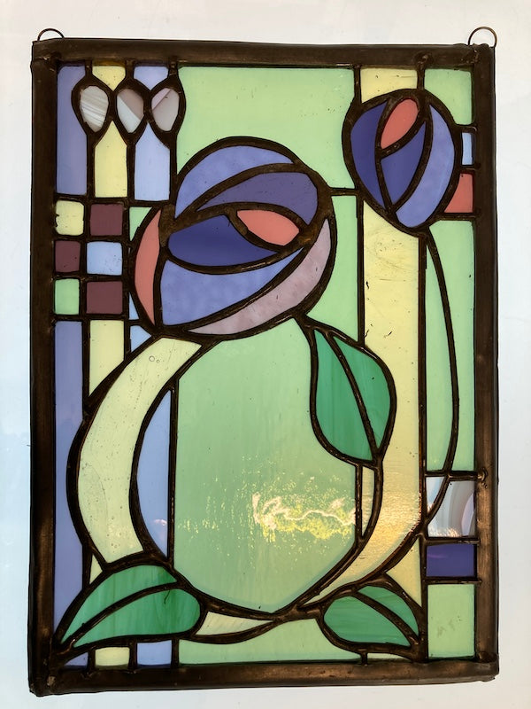 A Charles Rennie Mackintosh inspired stained glass hanging, with roses and leaves over a geometric design. Handmade by Dadswell Glass at Glass Designs in Bristol.