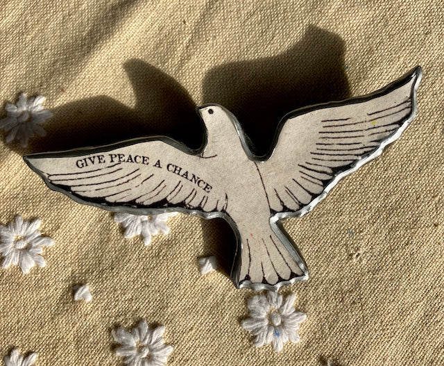 Give Peace a Chance dove brooch.  Made from layered paper and metal with resin to seal.