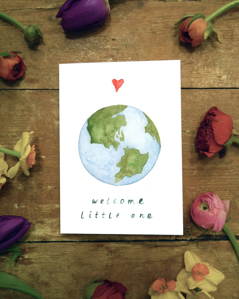 watercolour greetings card with the world and a heart and the words ''welcome little one''