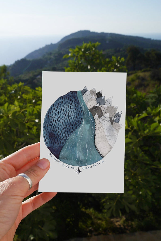 card with round blue watercolour of mountains dark sky and forest with the words ''mountains to climb oceans to swim''