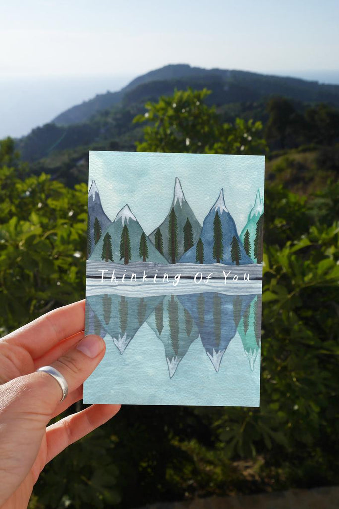 watercolour greetings card with mountains and trees reflected in a lake and the words ''thinking of you''
