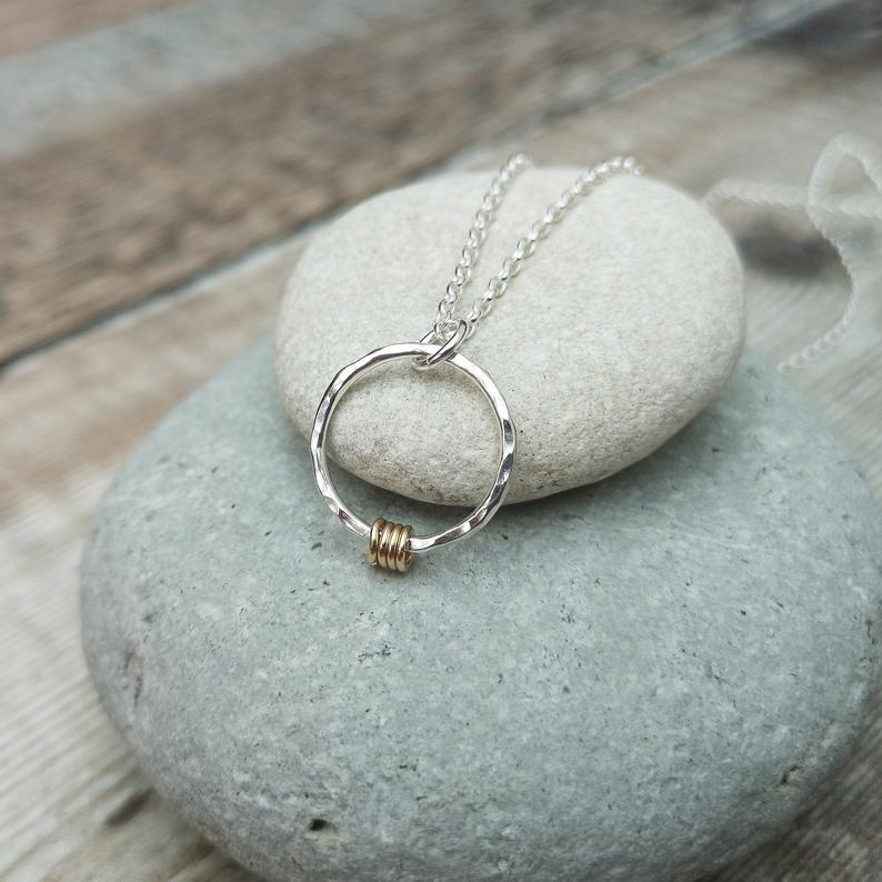 Glass Designs Jewellery By Jo necklace with open circle of hammered silver with 4 gold small hoops threaded onto the circle