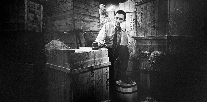 Gordon Segal, during the 1960s stands in a warehouse, surrounded by crates and barrels.