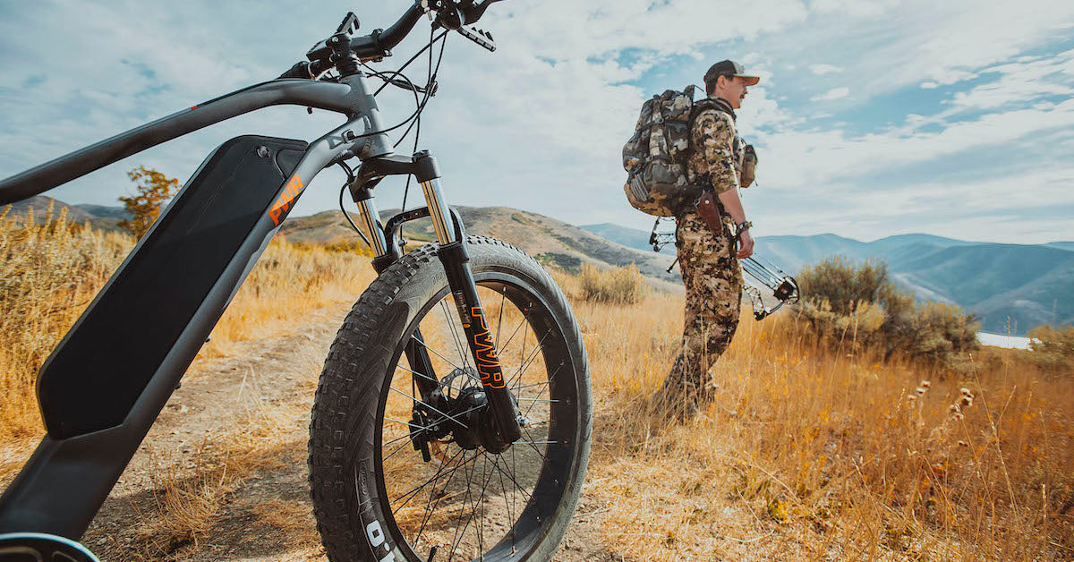 Hunter Outdoorsmen in the background PWR Dually e-bike in the foreground