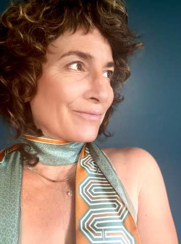 Image of designer and owner of At Home With Ray brand, Kris Roufa in one of her Eden silk scarves in earth tones