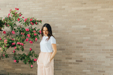 woman next to pink flowers in white sand 88 pants