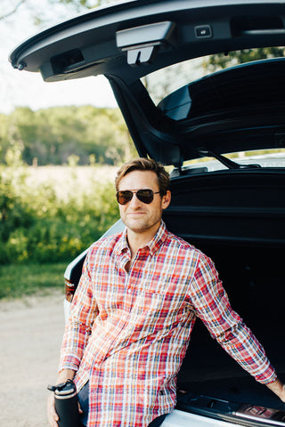 man standing in front of a luxury SUV holding coffee mug in plaid shirt