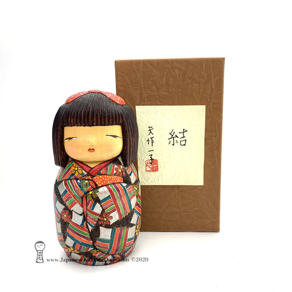 Kokeshi. Gorgeous, colorful, exquisitely hand-made Japanese kokeshi doll by Ichiko Yahagi. This doll, carefully handmade by award-winning artisan Ichiko Yahagai, is absolutely fabulousl Her geometric kimono is so detailed! And the quirky expression on her face is unlike the faces seen on any other kind of kokeshi doll. A true treasure! Rare and beautiful. One of a kind!