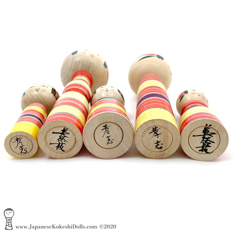 A photo showing the signature of kokeshi artist Takashi Kamata and Minae Kamata.