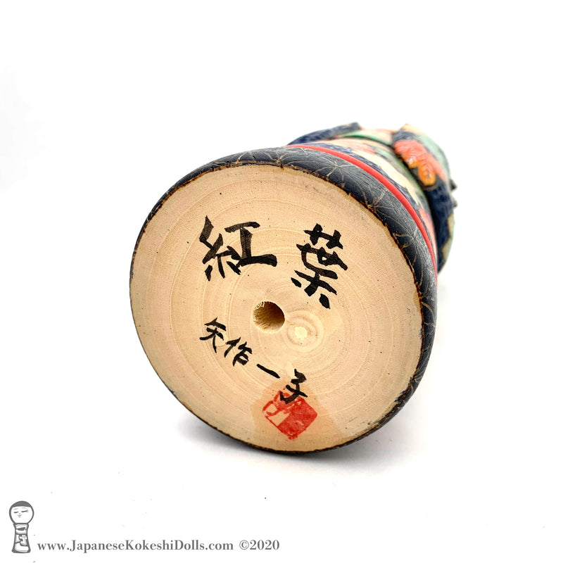 A photo showing the signature of kokeshi artist Kazuko Yahagi. The photo appears on the base of a one-of-a-kind modern kokeshi doll. The doll has a peaceful expression and is made from nicely grained hardwood.