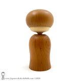 A rear view photo of an original, one-of-a-kind modern kokeshi doll by Isao Sasaki. Handmade from beautifully grained hardwood. A pretty kokeshi with a calm expression.