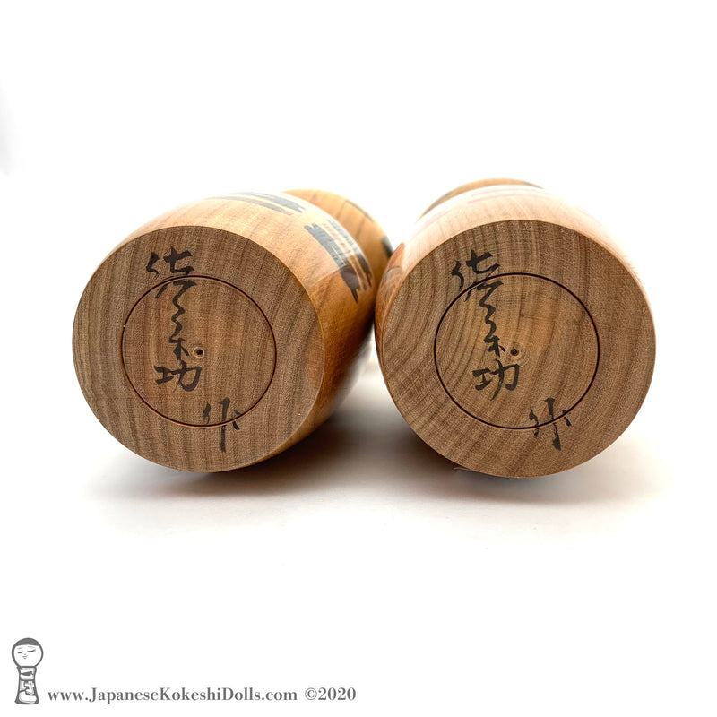A photo showing the signature of kokeshi artist Isao Sasaki. The photo appears on the base of a one-of-a-kind modern kokeshi doll. The doll has a peaceful expression and is made from nicely grained hardwood.