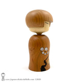 A side view photo of an original, one-of-a-kind modern kokeshi doll by Isao Sasaki. Handmade from beautifully grained hardwood. A pretty kokeshi with a calm expression.