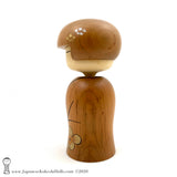 A side view photo (left side) of an original, one-of-a-kind modern kokeshi doll by Isao Sasaki. Handmade from beautifully grained hardwood. A pretty kokeshi with a calm expression.