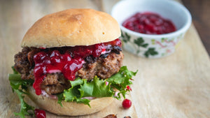 Moose burger with lingonberry jam on a wooden table