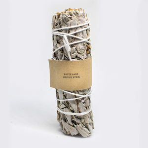 White sage smudge stick with a kraft label with black writing.