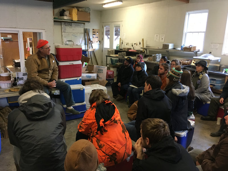 image shows Joel Salatin of Polyface farms wearing a bright orange beanie, sitting on coolers, addressing the class in the Polyface kitchen