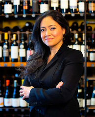 A front facing picture of co-owner of Despaña, Angelica Intriago, with her arms crossed in front of shelves of wine.