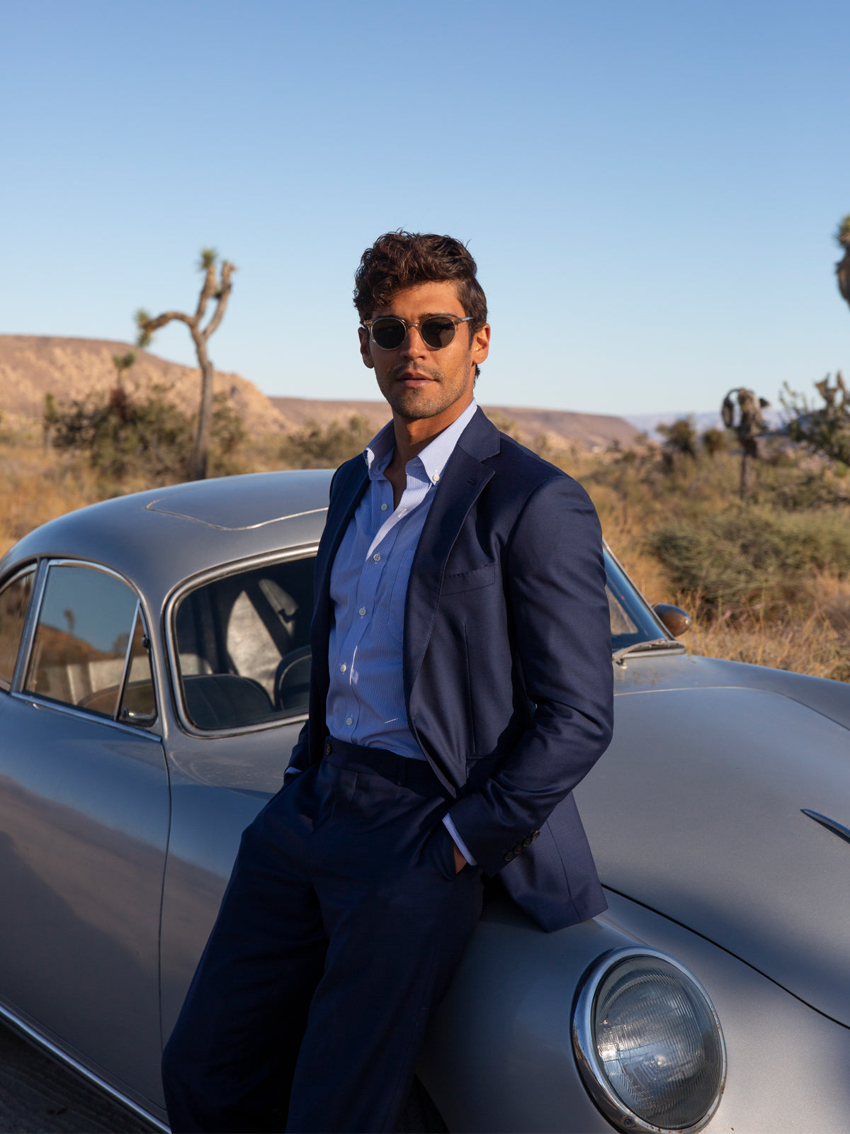 Model in suit leaning against car