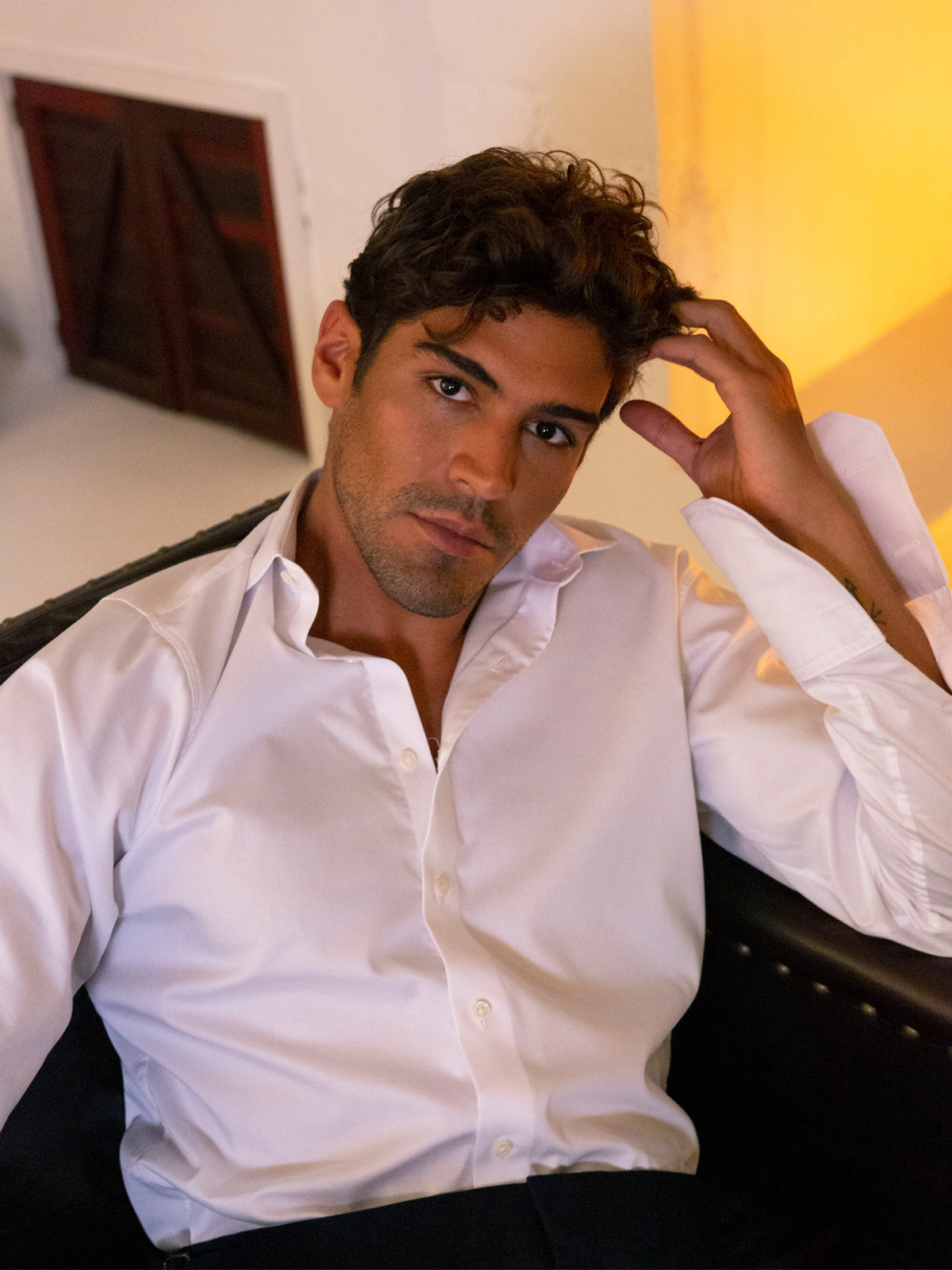 Model reclining in crisp white shirt