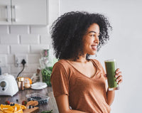 african american lady holding glass of green juice and smiling brown shirt in the kitchen