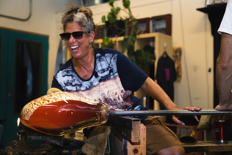 Glass blower Randi Solin smiles as she uses a propane torch to heat a large glass vessel