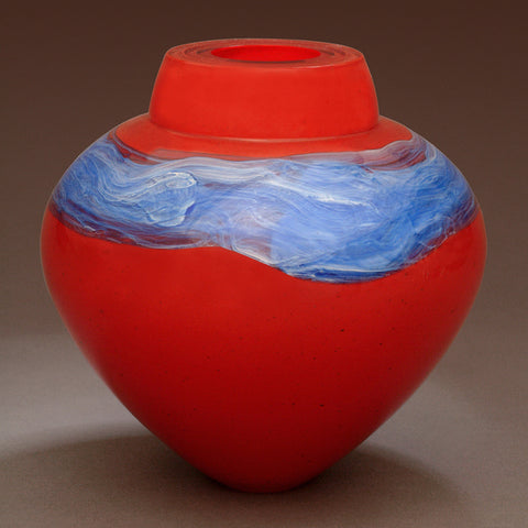 A bright red blown glass vessel with a band of silver blue glass stands against a gray background.