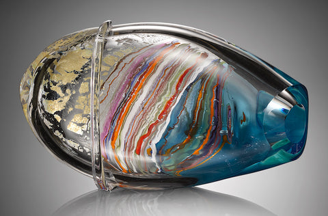A horizontal hand blown glass vessel featuring layers of shimmering silver leaf, bright blue glass, and streaks of white, red, orange, and purple glass cane stands against a gray background.
