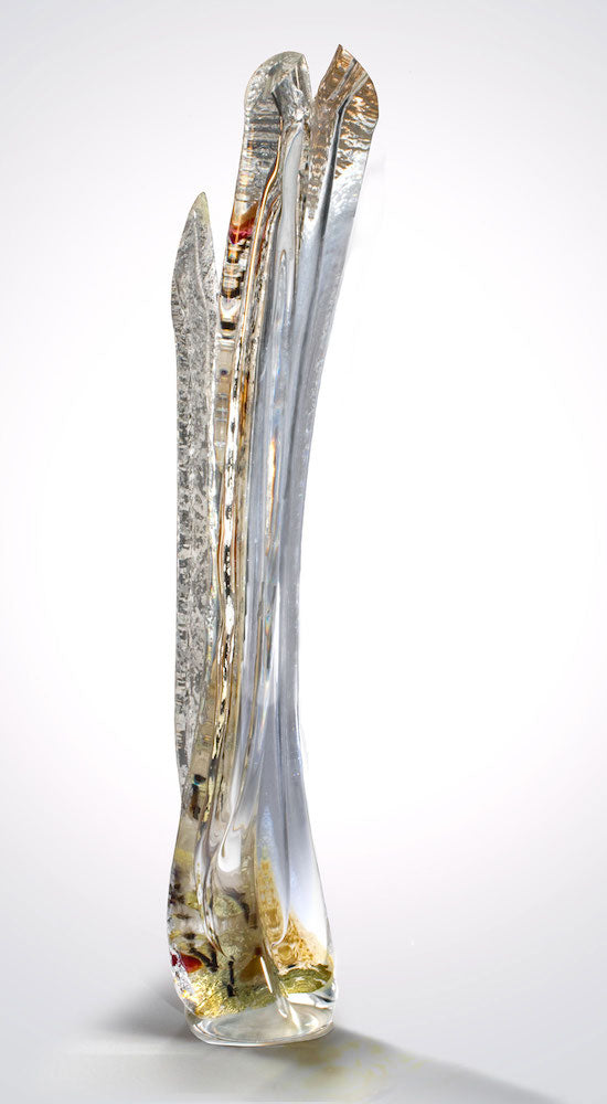 A tall hand blown glass sculpture features silver leaf and pops of red layered within thick clear glass.