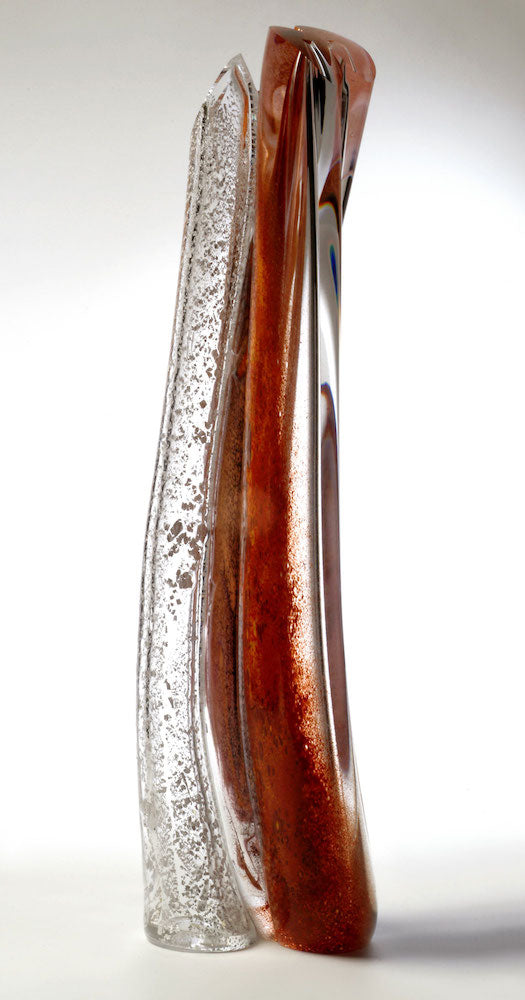 A tall hand blown glass sculpture featuring layers of red and silver in thick clear glass stands against a white background.