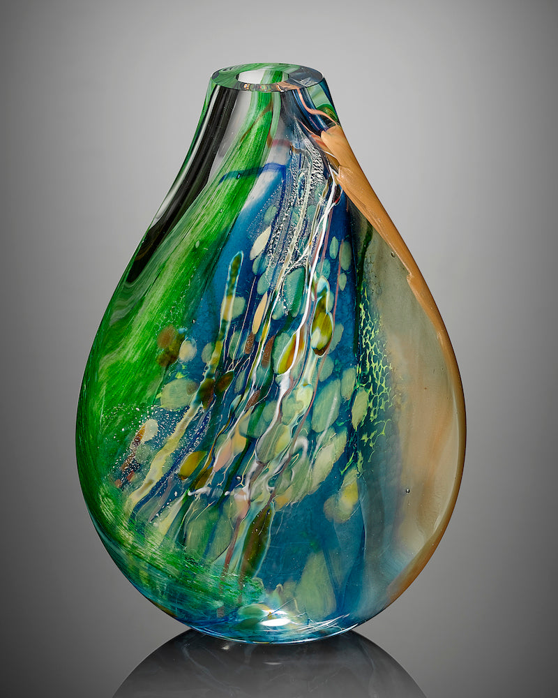 A sculptural blown glass vessel featuring blue, green, and clear glass stands against a gray background.