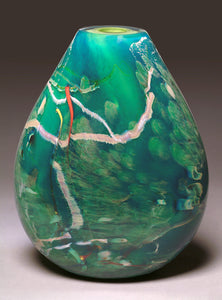 A hand blown glass vessel featuring layers of aquatic blues, greens, and veins of white glass stands against a light gray background.