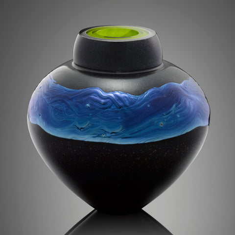 A black hand blown glass vessel features a band of silver blue glass and an interior layer of bright green glass.