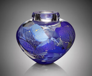 A thick clear hand blown glass vessel features five shades of blue glass with shimmering silver leaf.