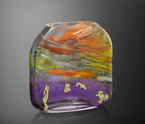 A large hand blown glass vessel molded into a square form features vibrant streaks of orange, yellow, red, and white glass cane in thick clear glass, featuring a band of orchid purple glass at the bottom with flecks of silver leaf.