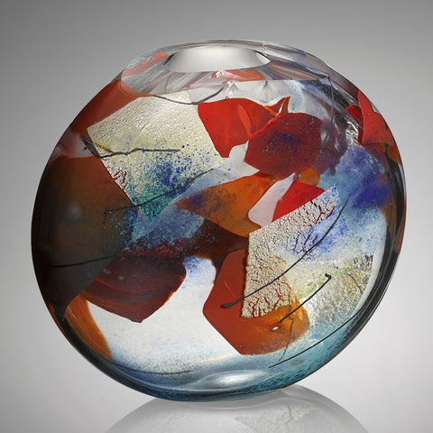 A thick clear hand blown glass vessel featuring shards of red and blue glass, layers of silver leaf, and veins of black glass cane stands against a gray background.