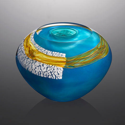A bright blue hand blown glass vessel featuring a sheet of silver leaf and a band of golden glass stands against a gray background.