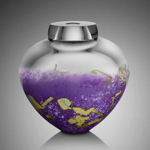 A thick clear hand blown glass vessel features vibrant purple glass on its bottom half, dotted with flecks of silver leaf.