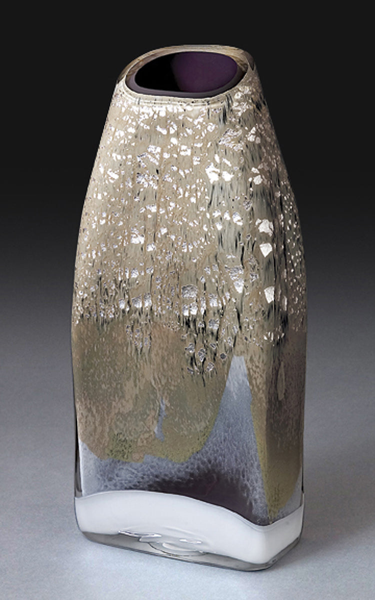 A tall rectangular blown glass vessel featuring shimmering silver leaf stands against a dark gray background