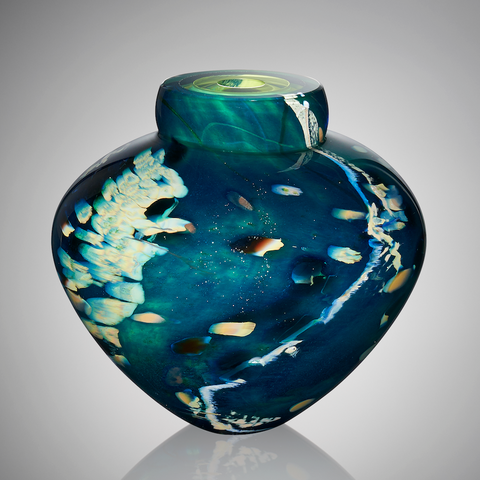 A hand blown glass vessel featuring layers of aquatic blues, greens, and flecks of silver stands against a light gray background.