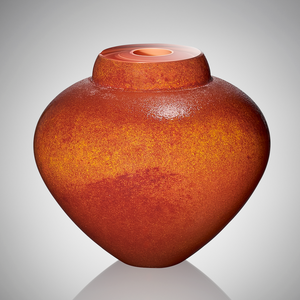 A hand blown glass vessel featuring lightly textured layers of orange, yellow, red, and apricot glasses to evoke the colors of a seashell.