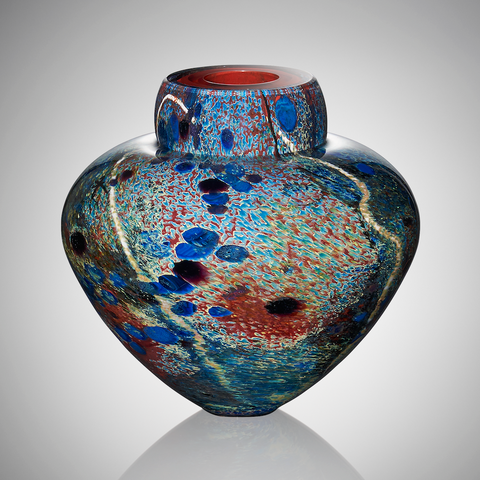 A colorful hand blown glass vessel with specks of red, blue, and green glass features a volcanic red interior and veins of white glass cane.