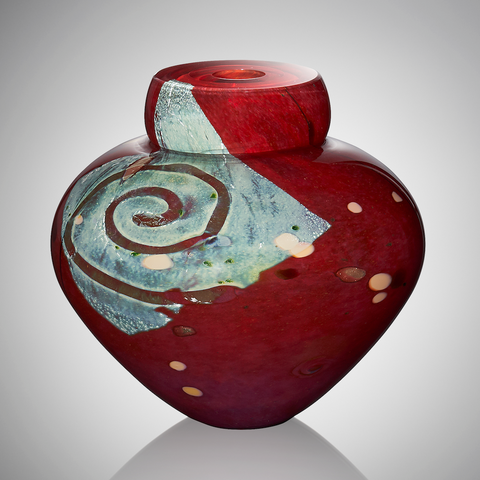 A deep red blown glass vessel features a square of silver leaf decorated with a swirl of clear glass, revealing the red coloration beneath. The surface is adorned with pops of burgundy and apricot glasses.