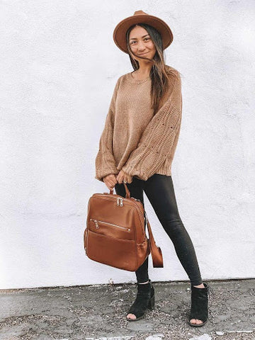 Woman holding leather diaper bag