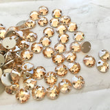 real photo of a group of Swarovski round sew on flat back elements in Golden Shadow colour