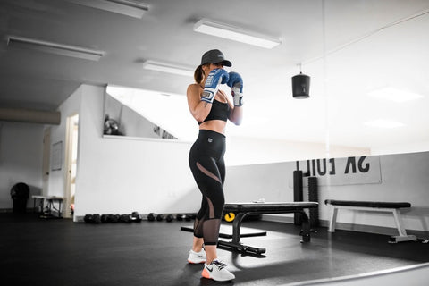 Woman wearing a crop top and high-waisted leggings while working out