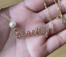 Load and play video in Gallery viewer, Custom Gold Name Necklace with Off White Freshwater Pearl. Personalized Pearl Name Necklace in 14k Gold. Script Name Brooklyn Necklace Pearl