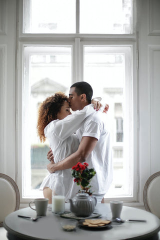 man kissing a woman on the forehead near the breakfast table in the morning