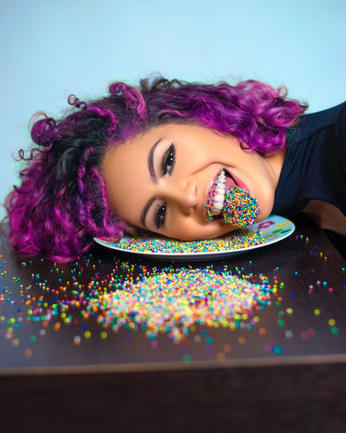 A woman with purple hair posing with sprinkles on her tongue