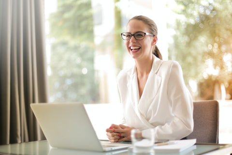 a woman beautifully smiling and a laptop in front of her